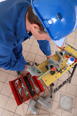 Plumber measuring pipe