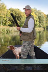 Hunter in a boat with a spaniel and a shotgun