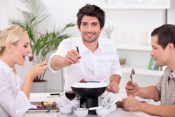 Friends enjoying chocolate fondue