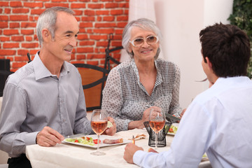 Young man and senior couple having a dinner in a restaurant