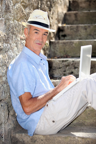 elderly gentleman working outdoors on laptop