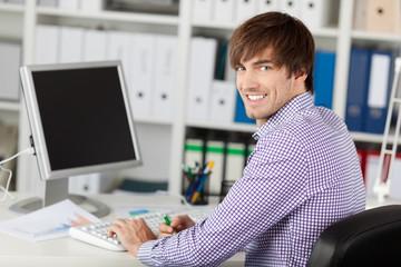 lächelnder geschäftsmann arbeitet am computer