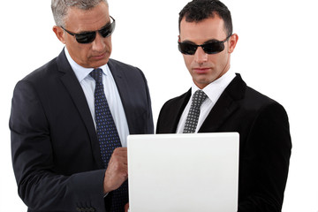 Serious men in smart suits with sunglasses holding a laptop