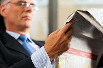 Chef in seinem Büro liest Zeitung