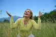 Pretty healthy summer woman outdoors on green field in Alps enjo