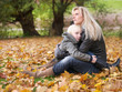 Blonde mother and daughter enjoy the autumn time outside