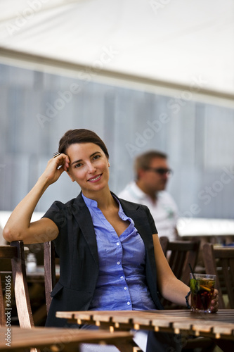 Pretty young woman sitting in garden of a restaurant