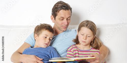 Leinwanddruck Bild Papa liest vor