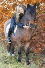 Young girl on horseback stroking a horse