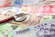 stethoscope and Background of asian currency