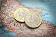 Closeup of Italy on a map and Euro coins
