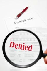 a blank credit application and magnifying glass with Denied text