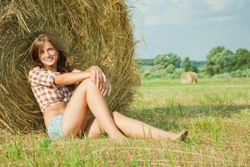 girl  resting on straw bale