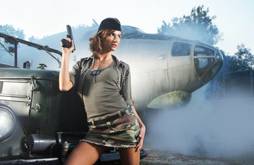 A young Caucasian woman in military clothes near a plane