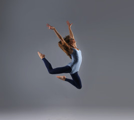 A young Caucasian female dancer caught in a jump