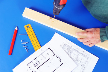 Carpenter`s hand with blueprints and drill machine