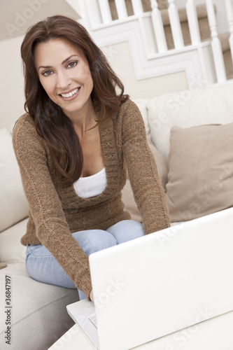 Brunette Woman Using Laptop Computer At Home on Sofa