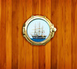 Brass portholes with view to the old sailing vessel
