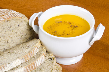 Bowl of Carrot Soup and Sliced Herb and Olive Bread
