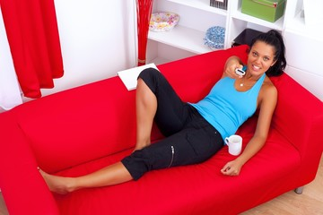 Woman with remote control on the sofa