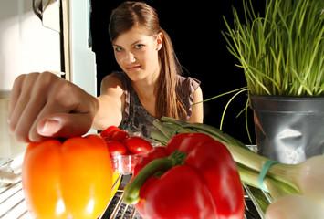 Mädchen holt Gesmüse aus dem Kühlschrank