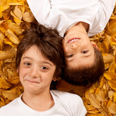 Two kids, 6 year old, laughing, lying on leaves.