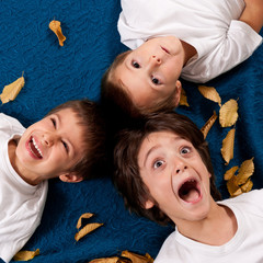 Three kids laughing, lying on leaves