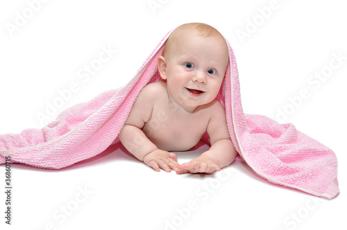 Smiling child 7 months peeks out from under the towel