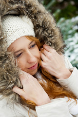 Portrait of pretty girl at winter background wearing warm clothe