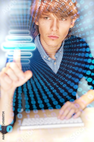 Young business man pressing a touchscreen button while working a