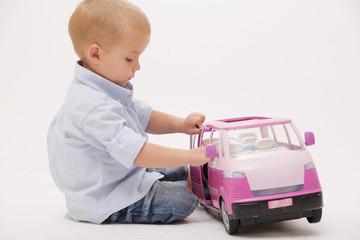Cute boy playing with toy car.