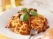 spaghetti with basil garnish in meat sauce closeup