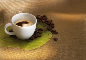 Caffè con chicci su foglie e juta