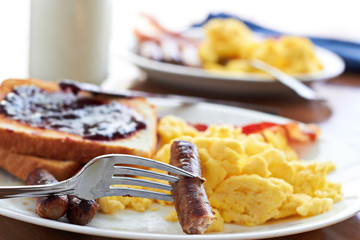 sausage links being pick up by a fork at a big breakfast.