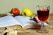 Offenes altes Buch mit Herbstlaub und Rotweinglas