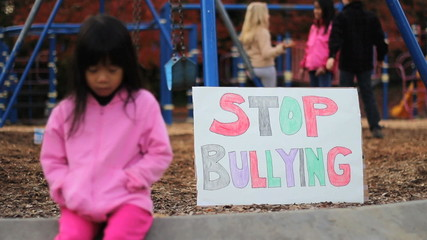 Frightened Girl With Stop Bullying Sign At School