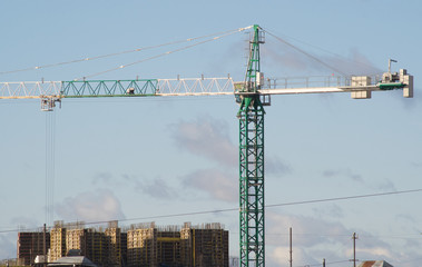 Green and white hoisting crane on building construction