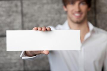 lächelnder mann zeigt weißes schild