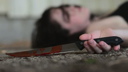 Conceptual footage of a dead woman holding a sharp knife