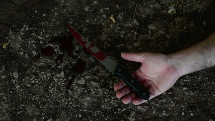 Conceptual footage of a hand holding a sharp knife