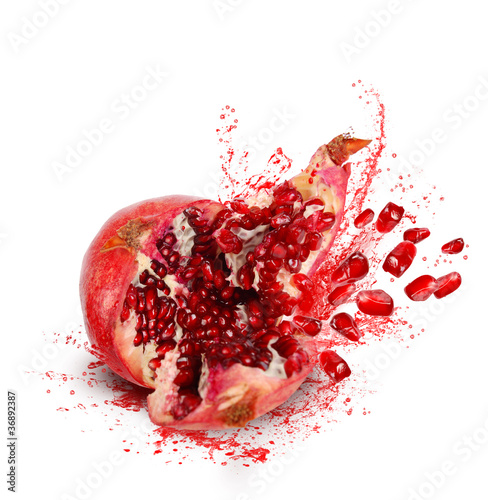 Falling and crack pomegranate with splashes of juice and seeds
