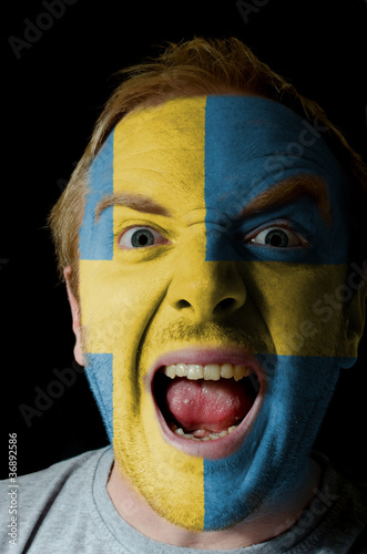 Face of crazy angry man painted in colors of sweden flag