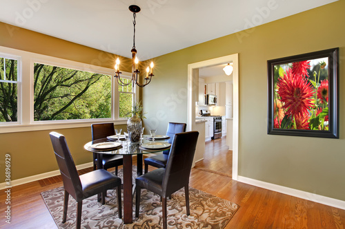Classic dining room with leather chairs and glass table.