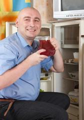 man putting jug with fruit-drink