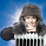 Young woman with pelt cap leans over a radiator outside poster
