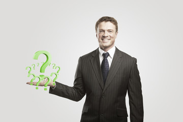 Young  businessman with a question marks on his hand