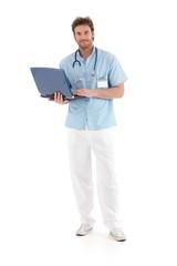 Goodlooking doctor working on laptop smiling