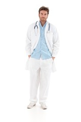 Confident doctor standing with hands in pocket