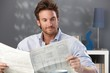 Handsome man reading newspaper