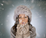 A young woman blowing snowflakes